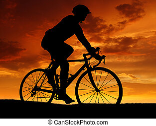 cyclist riding a road bike - silhouette of the cyclist...