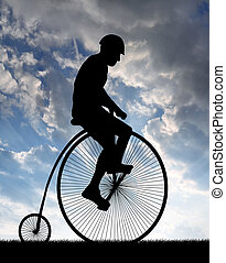 cyclist on historic bicycle - silhouette cyclist on historic...