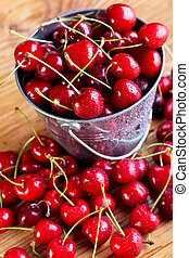 Fresh cherries in a small bucket - Fresh cherries on wooden...