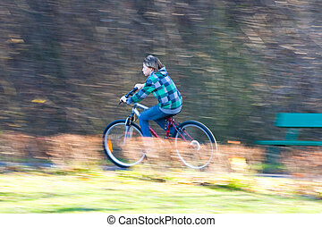 Mountain biking in a park - Young biker on a park biking...