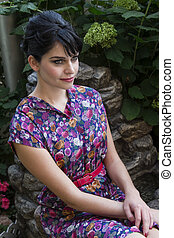 Sitting in the garden - Young woman wearing a multi colored...