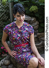Young woman in garden - Young woman wearing a multi colored...