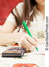 Calculations - Female hand writing and making calculations