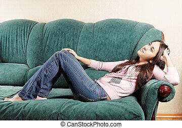 Brunette relaxed on green sofa