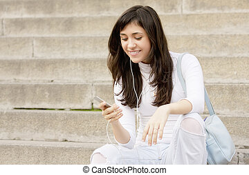 Young woman listening music while sitting on steps
