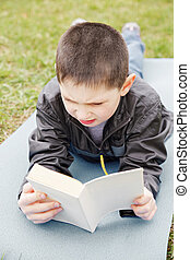 Little boy reading book outdoors