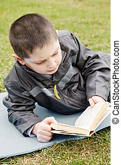 Kid reading book outdoors