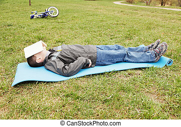 Nap on grass - Little boy have a day nap on grass
