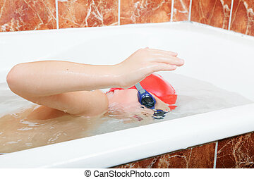 Crowl swimming in bath - Little boy in cap and goggles crowl...