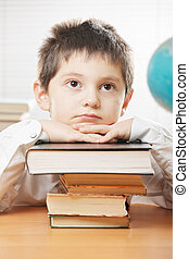 Boring boy leaning on stack of books - Boring boy sitting at...