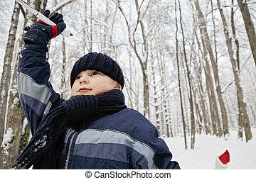 Boy ski running in winter forest closeup