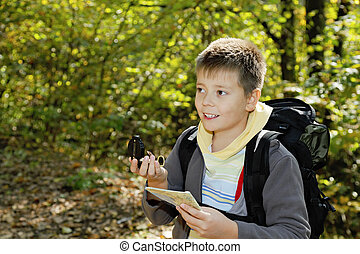 Smiling boy orienteering in forest - Smiling boy with compas...