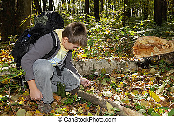 Boy setting fire with magnifying glass in autumn forest