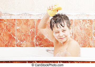 Boy taking bath holding soapy sponge over head