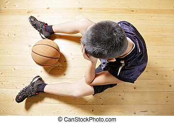 Kid with basketball on floor - Kid with basketball sitting...