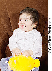 Smiling baby with soft toy looking sideways