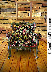 Antique armchair in the brick wall room with a frame hanging on.