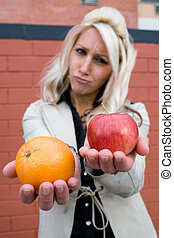 Apples and Oranges - A young woman compares an apple to an...