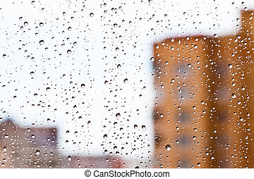 rain drops on window with city houses background