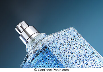 Perfume in blue bottle with water droplets