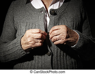 Old hands of an unrecognizable senior woman buttoning her...