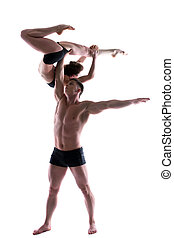 Couple of young graceful acrobats posing in studio