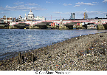 Low tide River Thames and London city skyline including St...