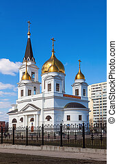 White cathedral with golden domes of the forged fence on a sunny day in Samara, Russia