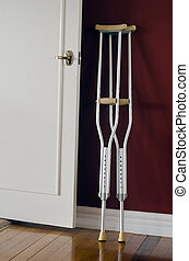 A pair of crutches lean on a wall at home