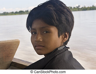 628 Amazon Boy riding in a river boat on the Amazon River -...