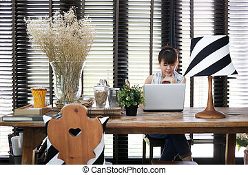 Young asian working woman is using a laptop with vintage...