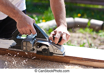 Carpenter with electric planes - Worker planed Board...