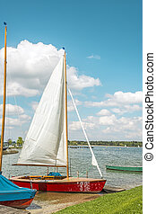 Red sport sailboat in the lake Chiemsee in bright sun