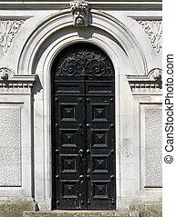 Ancient black door - Closed wooden black door on old ancient...