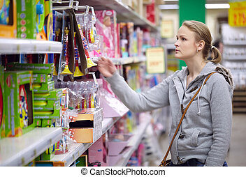 Young woman is choosing toys for her kid Middle shot