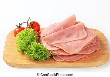 Thinly sliced ham on a cutting board