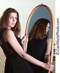 thoughtful woman looks at the reflection in mirror -...