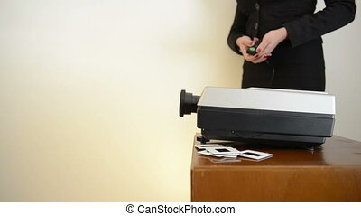 Slide Projector Woman - Woman operating a slide projector,...