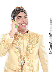 man with traditional java suit using mobile phone