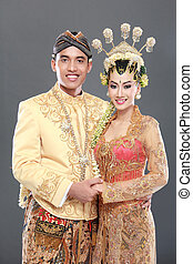 traditional java wedding couple husband and wife hold each...