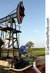 oil worker with pipe wrench and pipeline