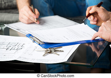 Two people signing a document - Hands of two men signed the...