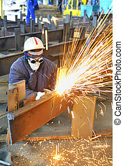 worker using torch cutter to cut through metal in factory