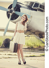 Lonely girl with suitcase at near airplane. Photo in old...