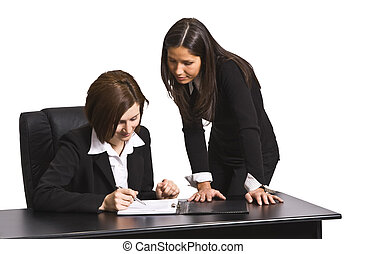 Working together - Two businesswomen working together in an...