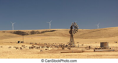 Old broken wind pump and new wind generators distorted by...