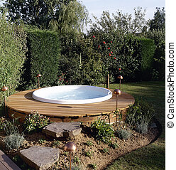 Beautiful outdoor jacuzzi in the backyard garden provides...