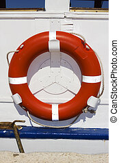 Orange ring buoy hanging on white painted boat