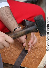 expert craftsman working leather with awl and hammer