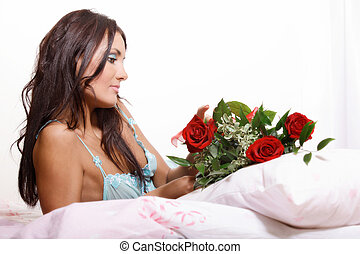 Beautiful sexy woman lying on bed in lingerie holding red roses. Selective focus